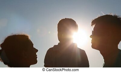 silhouettes of family with boy against sun - silhouettes of...
