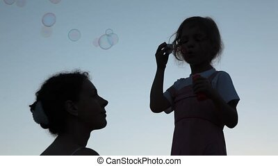 mother and little daughter blowing up soap bubbles