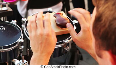 man of brass band plays castanets sitting on sunny summer...
