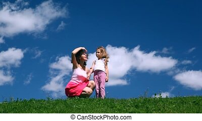Woman with girl sits on hill