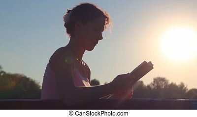 woman sitting on bench and reading book against sunset sky