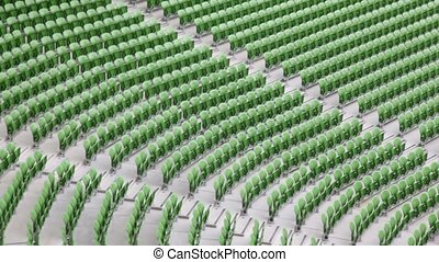 Many rows of seats in stadium. - Many rows of green,...
