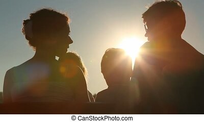 family sits on bench against evening sky - family of four...