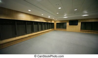 Locker room for sportmen, subdued light, a TV is situated on...
