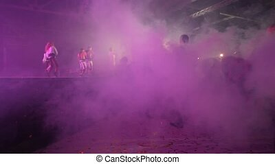 Dancers appear on illuminated stage in smoke