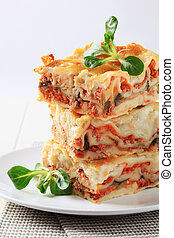 Lasagna - Stack of lasagne garnished with salad greens