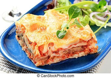 Lasagna - Portion of lasagna garnished with salad greens