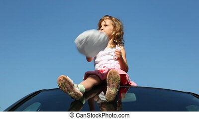 Little girl sits at roof of car against sky