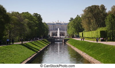 Alley of trees and channel in middle front Royal Petrodvorets