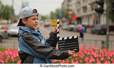 Boy claps clapperboard and goes out of frame at bed with tulips on city streets