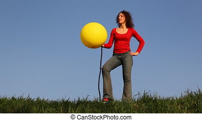Girl stands in meadow and blows up foot pump balloon