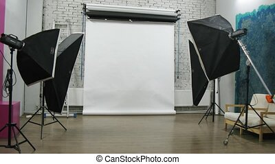 Photographer and his kid adjust lightening at photo studio...