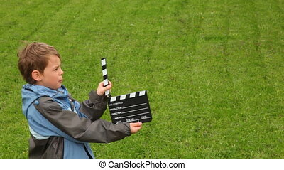 Boy says, claps clapperboard on grass
