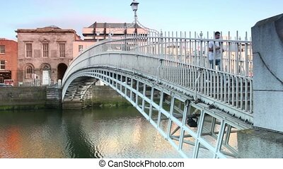 People crosses The Hapenny Bridge through the Liffey river -...