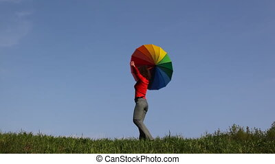 Woman with rainbow umbrella turns on grass