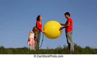 man stands on green grass holding large yellow balloon, his wife and little daughter pump up it foot pumps