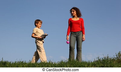 Boy with clapperboard stands before mother on grass