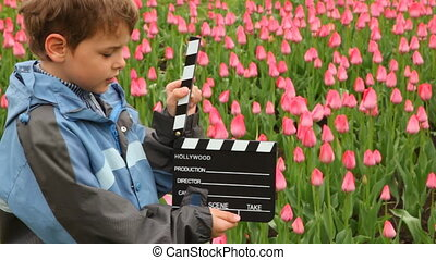 Boy says, claps clapperboard on many pink tulips field