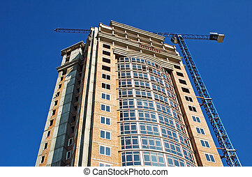 Crane and highrise construction sit
