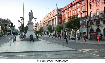 Street traffic, people and cars around monument near central Post office on O'Connell street