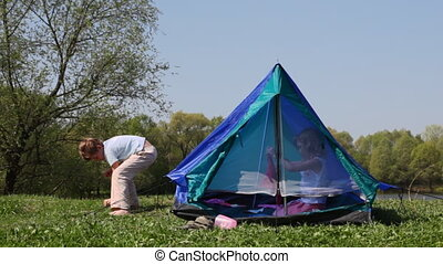 Boy strengthens tent cables, girl opens zipper mosquito net...