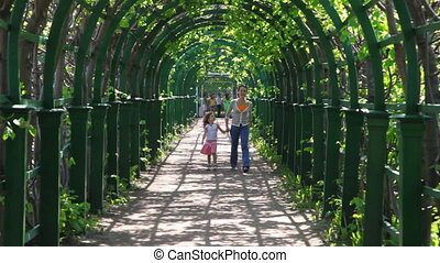 Mother and little daughter go through arched corridor...