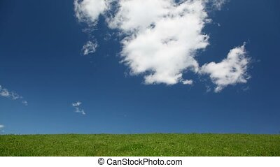 White clouds move across sky above green hill