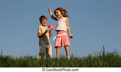 Boy shakes rattle in form of hands, and his sister dances -...