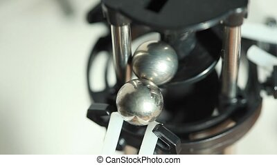 Closeup of two iron balls lift and drop with mechanism -...