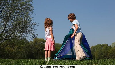 Boy and little girl put up tent in woods - boy and little...