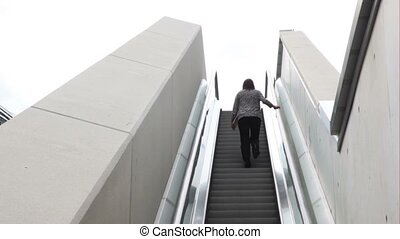 A woman is going upstairs by the escalator.