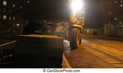 Loader-excavator board concrete slabs at street blocking way...
