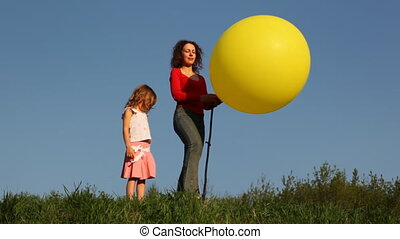 young woman with her little daughter stand on green grass against blue sky and blow up foot pump yellow balloon
