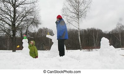 Kids and dad sculpt three snowmans, time lapse - Two little...