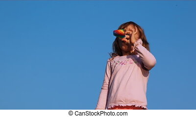 Little girl blows in party blower on sky - nice little girl...