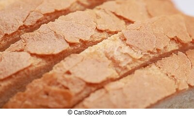 Closeup of sliced bread, it rotate on white - closeup of...