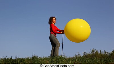 Woman stands in meadow and blows up foot pump balloon -...
