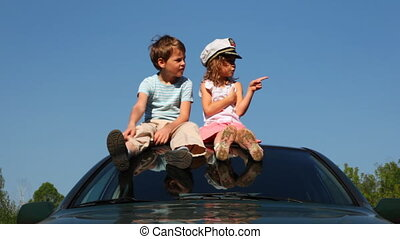 Boy and girl sit on roof of car - boy and little girl in...
