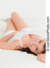 Attractive brunette female posing while lying on a bed