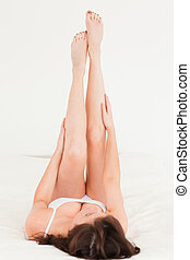 Beautiful brunette female stretching her legs while lying on...