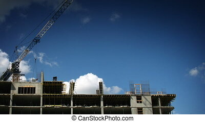 Construction crane working against the blue sky and clouds