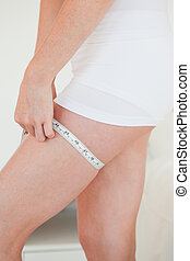 Woman measuring her hip with a tape measure while standing