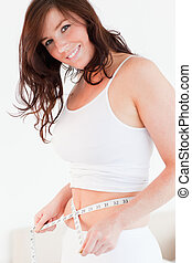 Attractive brunette woman measuring her belly with a tape measure