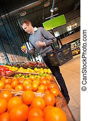 Man in Supermarket Buying Fruit - Man carrying basket while...