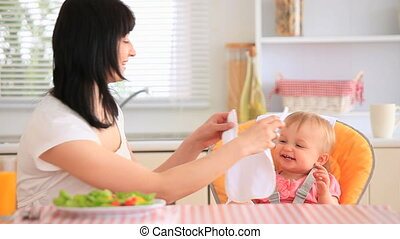 Young mother feeding her daughter