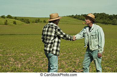 shaking hands - two farmers shaking hands in a field