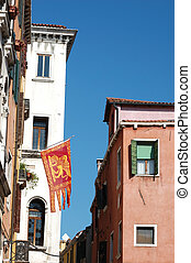 Old houses and symbol of Venice- flag with Saint Mark lion