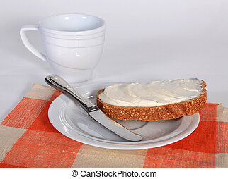 Appetizing sandwich with butter on the white saucer