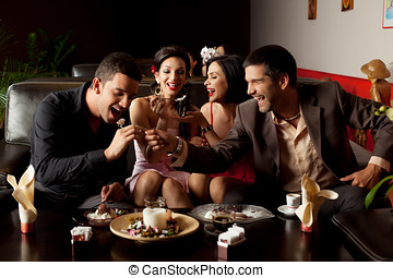 ice-cream fun at the restaurant lounge - young couples...