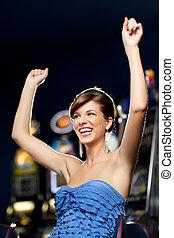 glamourous woman celebrating winning - young woman playing...